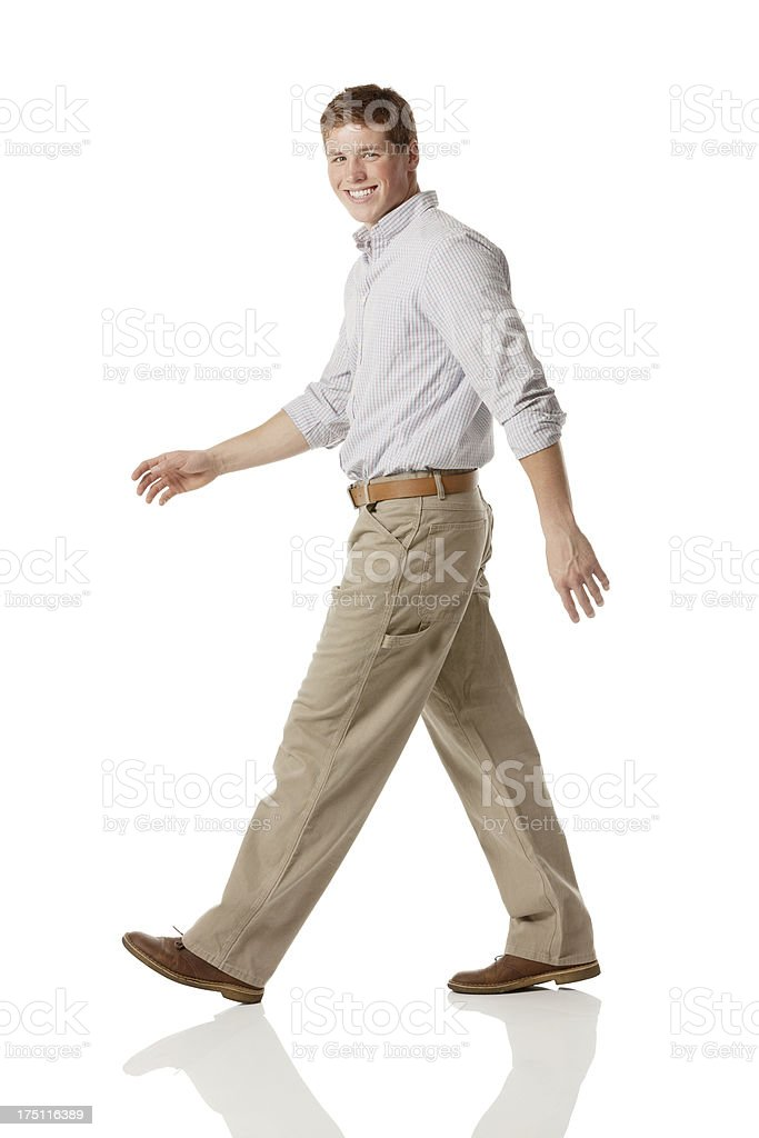 Side view of a smiling young man walking royalty-free stock photo