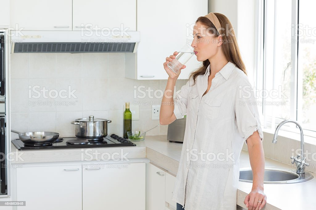 Side view of a woman drinking water in kitchen stock photo