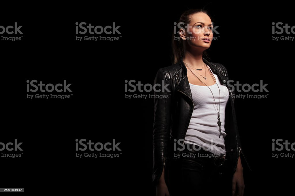 side view of a  woman in leather clothes looking up stock photo