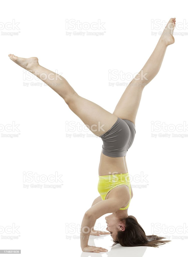 Side view of a woman performing headstand stock photo