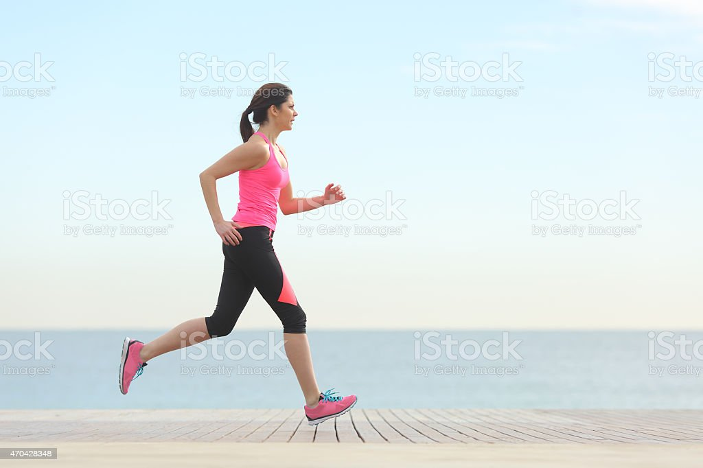 Side view of a woman running on the beach stock photo