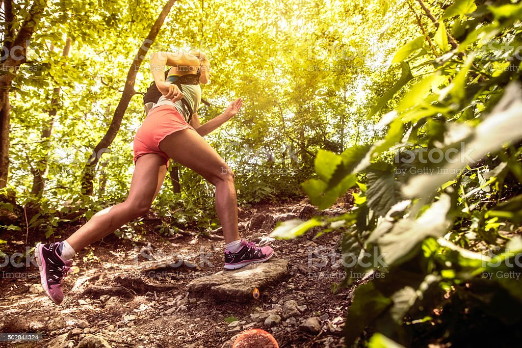 Side view of a woman running uphill in a forest stock photo