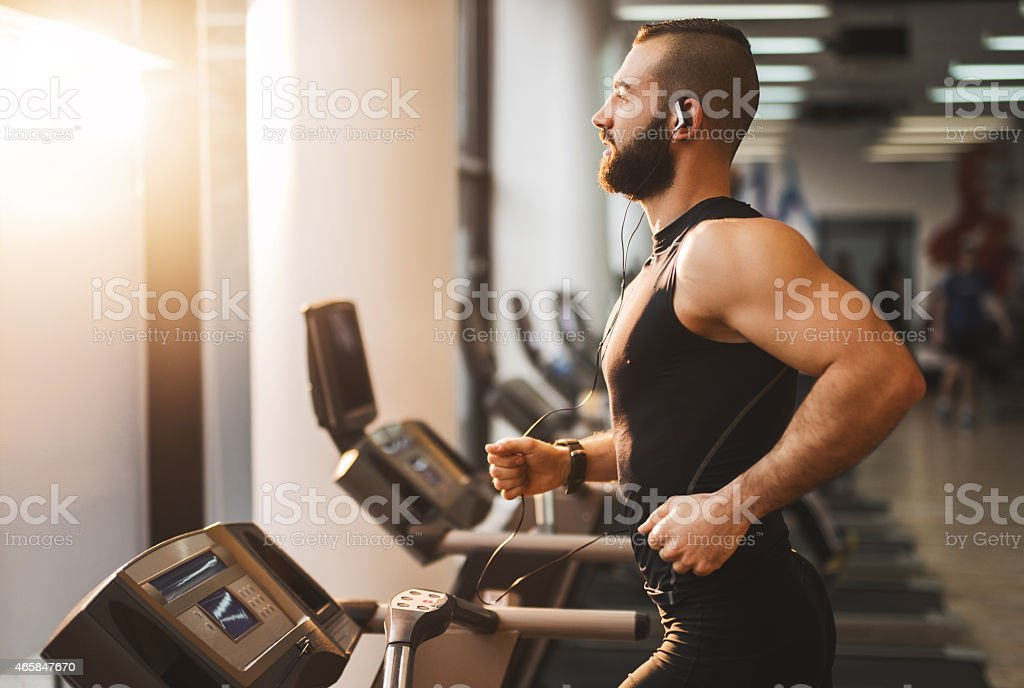Side view of a young athlete running on treadmill. stock photo
