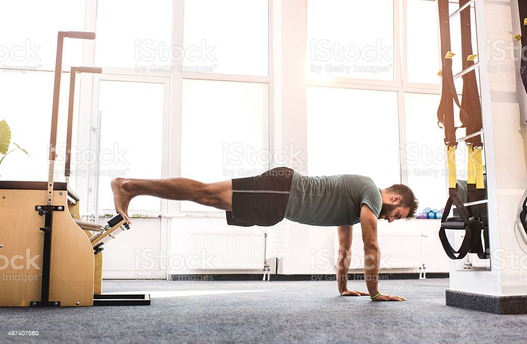 Side view of a young man exercising with Pilates machine. stock photo