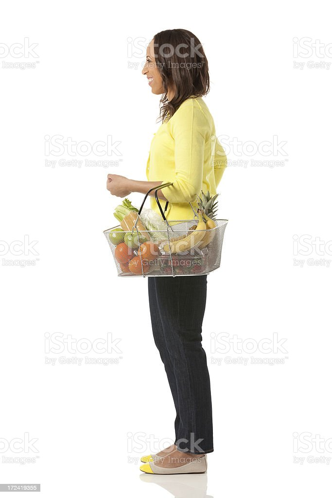 Side view of a young woman with fruit basket royalty-free stock photo