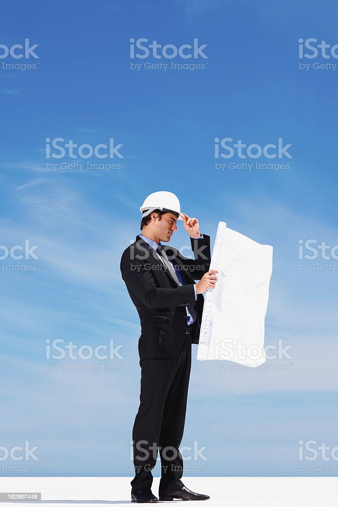 Side view of an architect standing while holding a blueprint royalty-free stock photo
