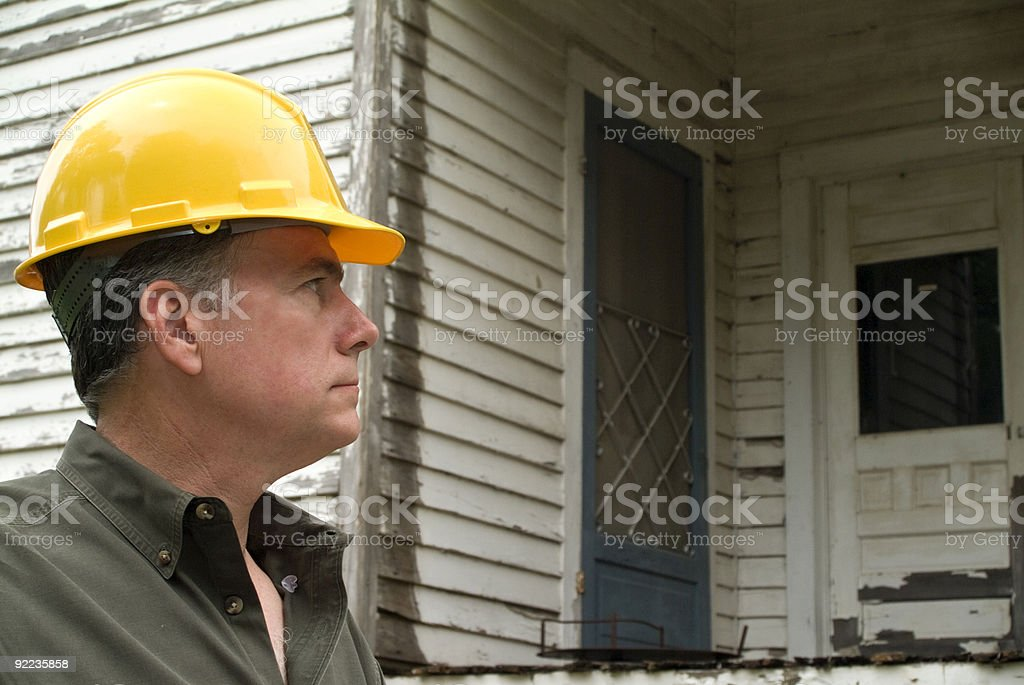 Side view of an inspector in yellow hard hat outside a house royalty-free stock photo