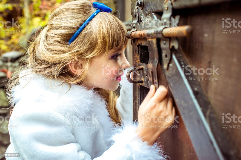 Side view of an little beautiful girl in the scenery of Alice in Wonderland looking into the keyhole of the gate stock photo