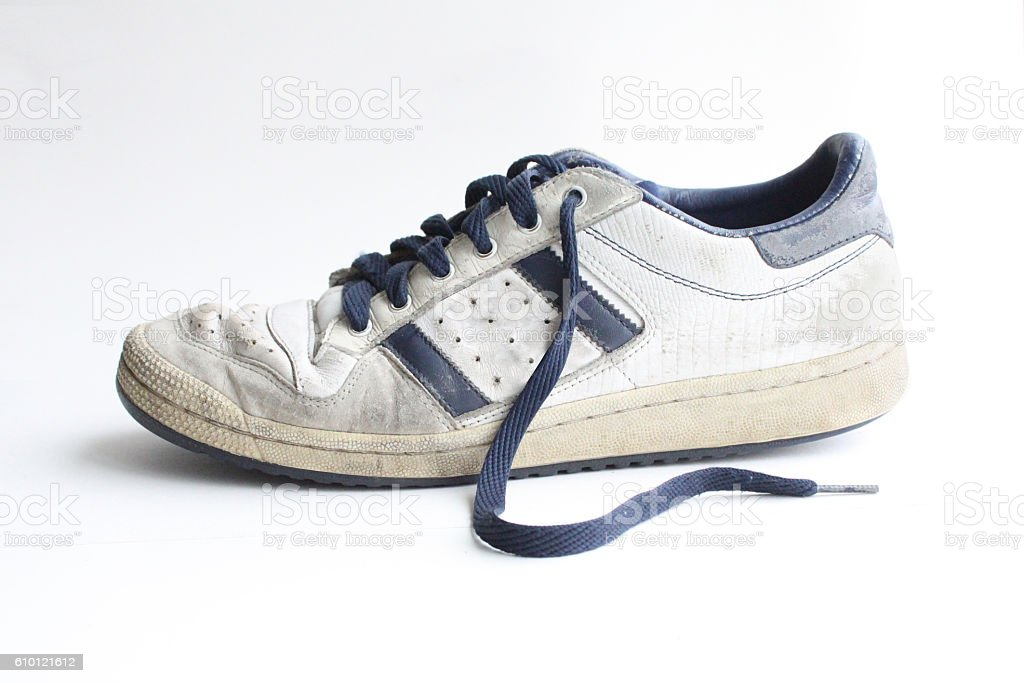 Side view of an old, worn, white vintage sneaker stock photo