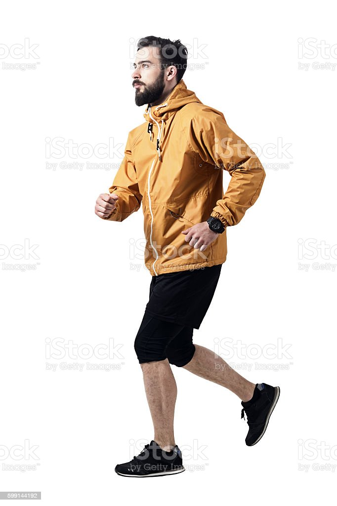 Side view of athletic man jogging in jacket looking up stock photo