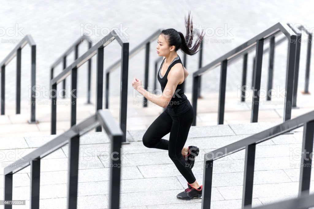 Side view of athletic young woman in sportswear running on stadium stairs stock photo