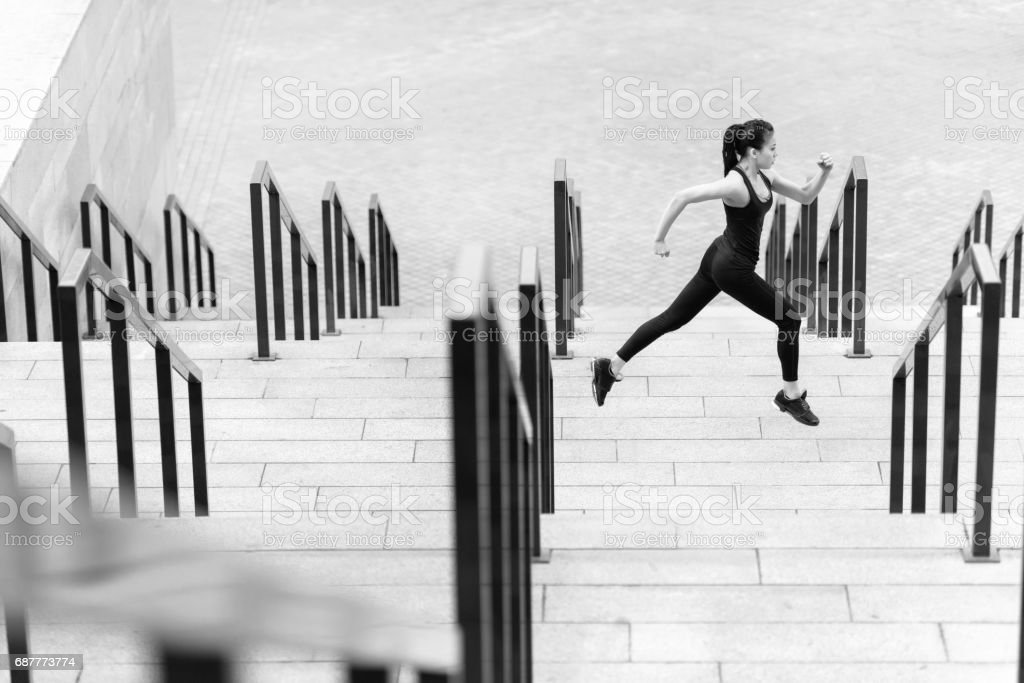Side view of athletic young woman in sportswear running on stadium stairs, black and white photo stock photo