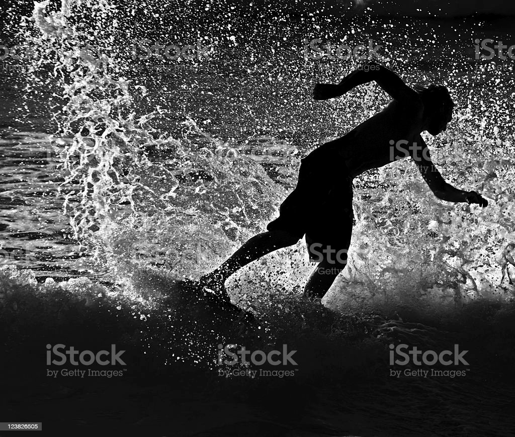 Side view of back lit skim boarder stock photo
