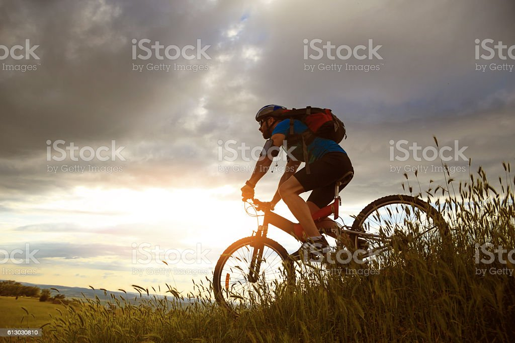 Side view of biker moving up on the mountain stock photo