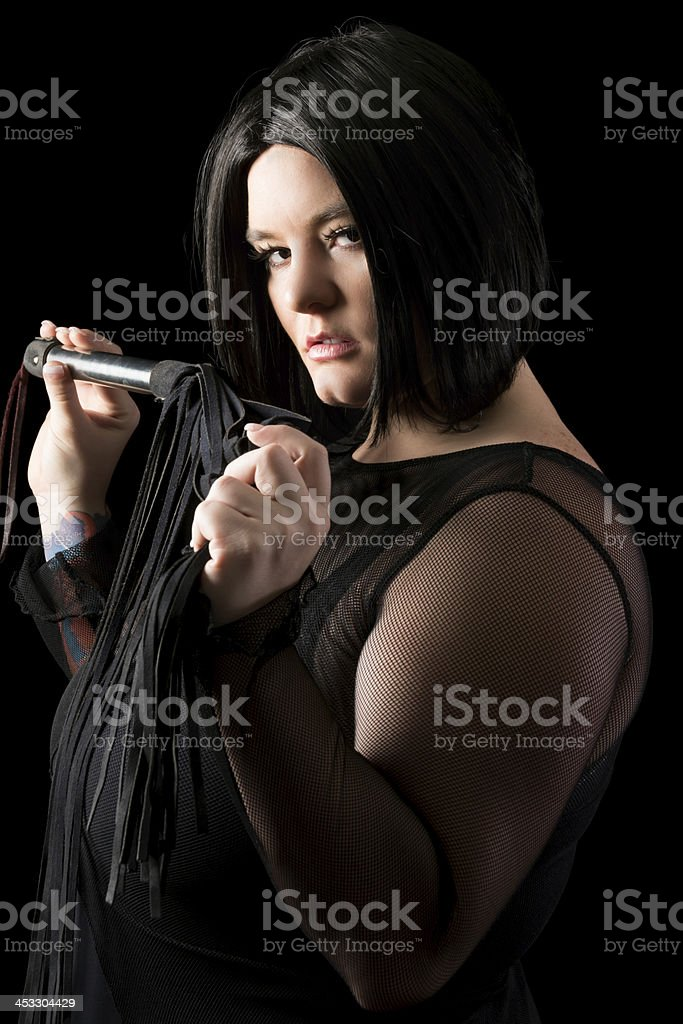 Side view of black haired dominatrix with flogger. stock photo