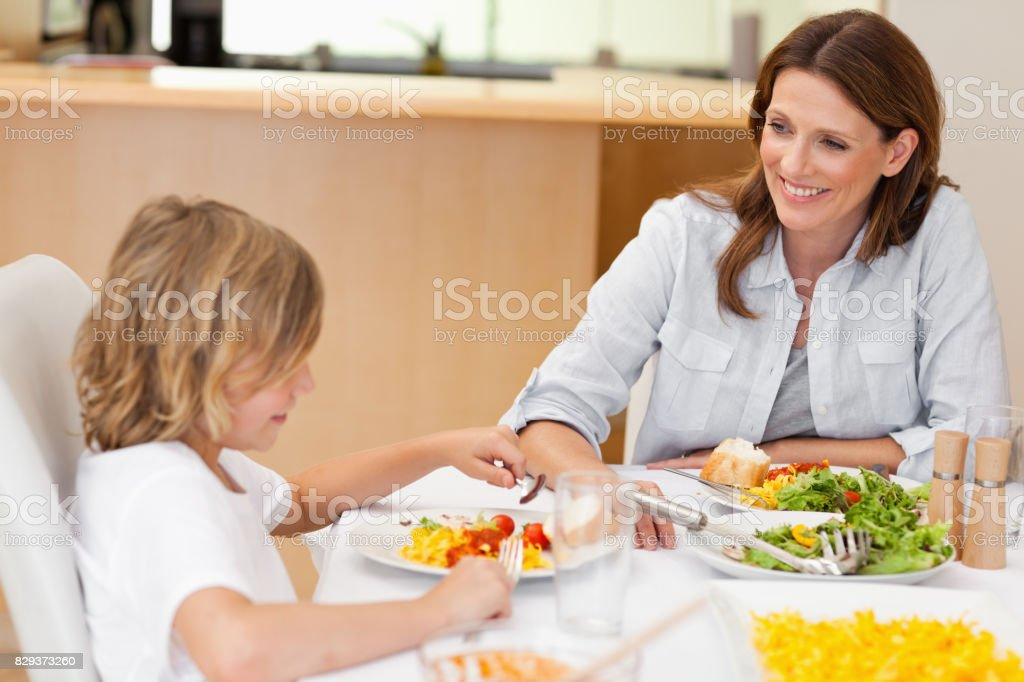 Side view of boy eating dinner stock photo