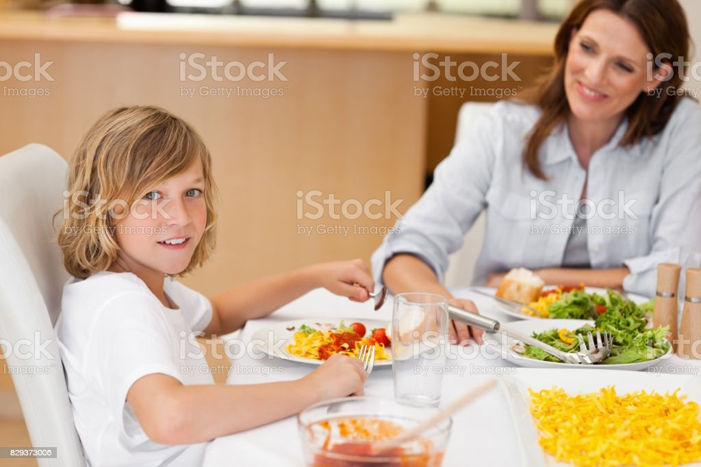 Side view of boy sitting at the dinner table stock photo