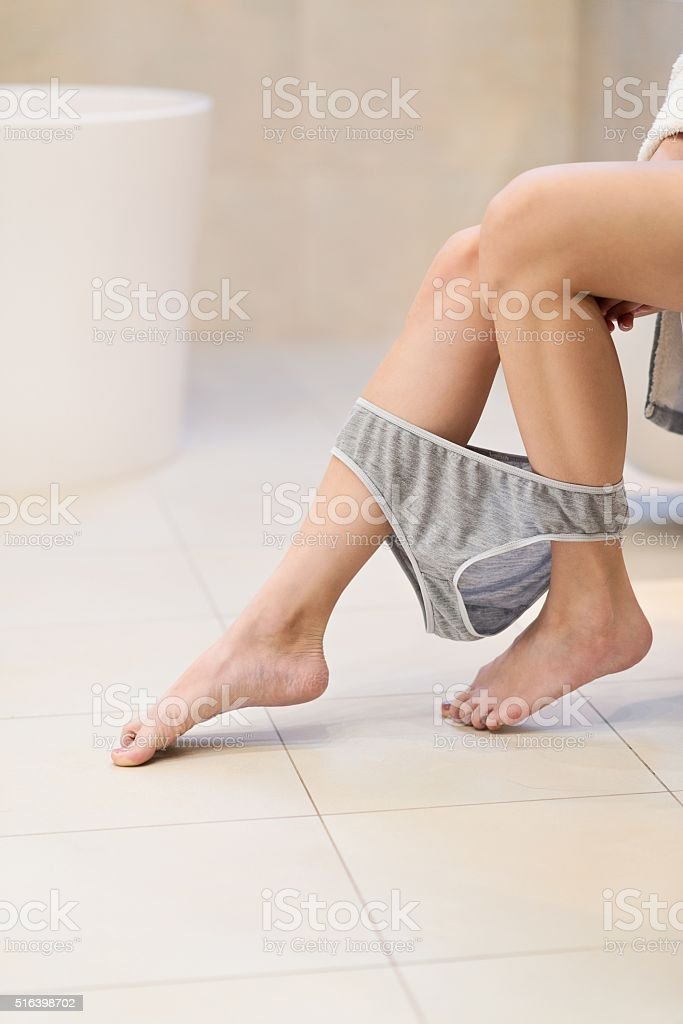 Side view of brunette woman sitting on toilet stock photo