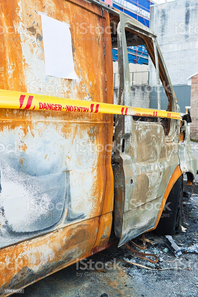 Side view of burnt down van with trespassing cordon tape stock photo
