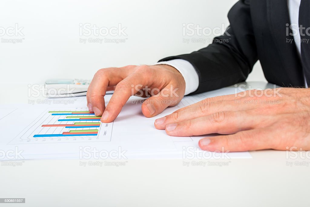 Side view of businessman analysing a set of bar graphs stock photo