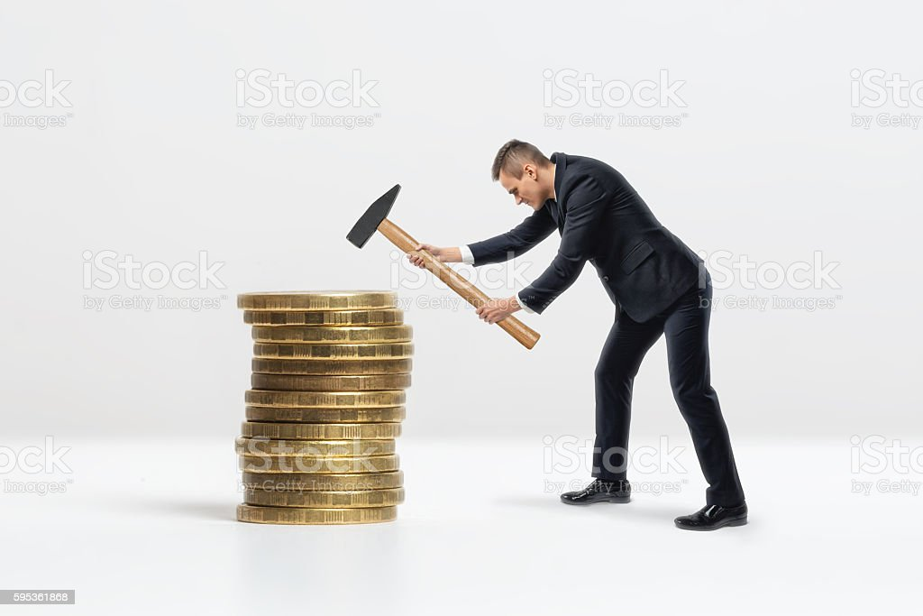 Side view of businessman crashing big golden coins stack with stock photo