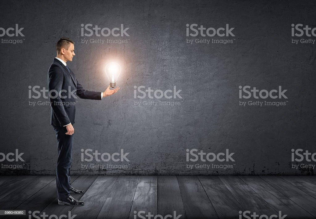 Side view of businessman standing and holding glowing light bulb stock photo