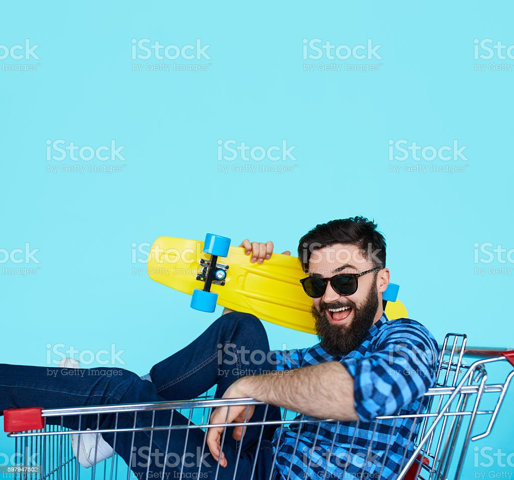 Side view of cheerful young man sitting in shopping cart stock photo
