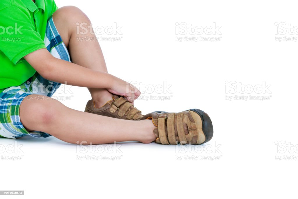 Side view of child put leather shoes on with copy-space. stock photo