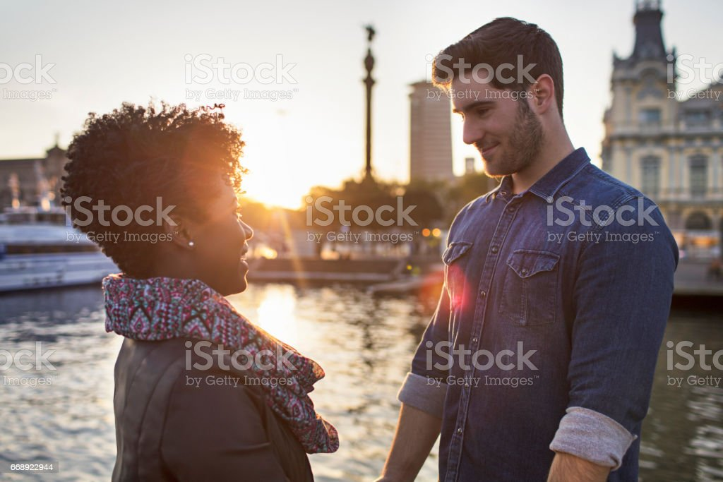 Side view of couple looking at each other by river stock photo