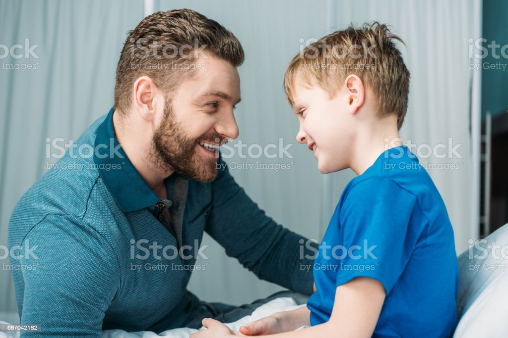side view of dad and son looking at each other in hospital chamber stock photo