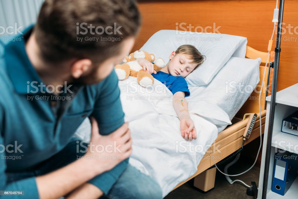 side view of dad sitting near sick son in hospital bed stock photo