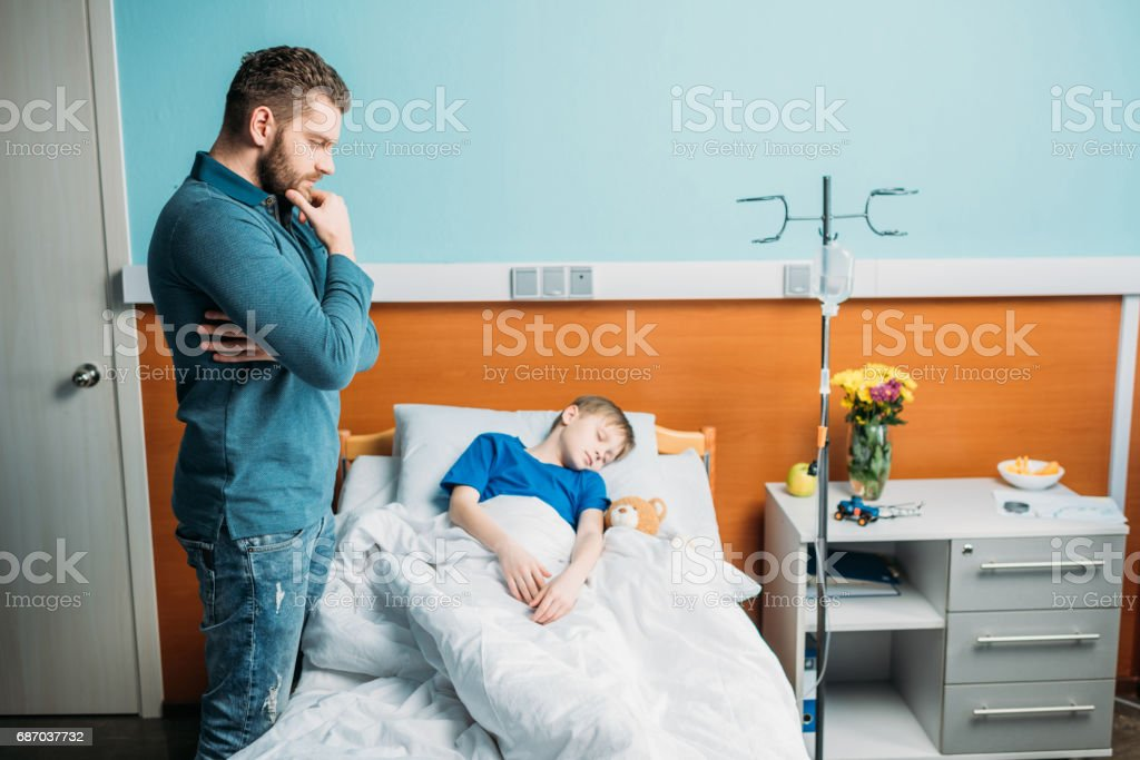 side view of dad standing near sick son in hospital bed stock photo