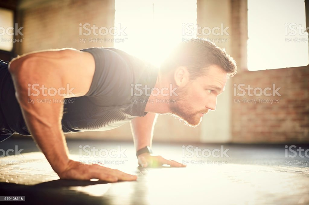 Side view of determined man doing push-ups in crossfit gym stock photo