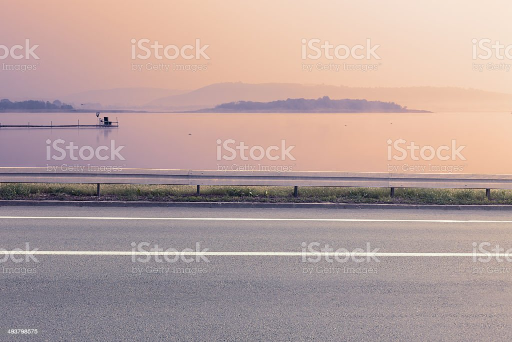Side view of empty asphalt road and lake stock photo