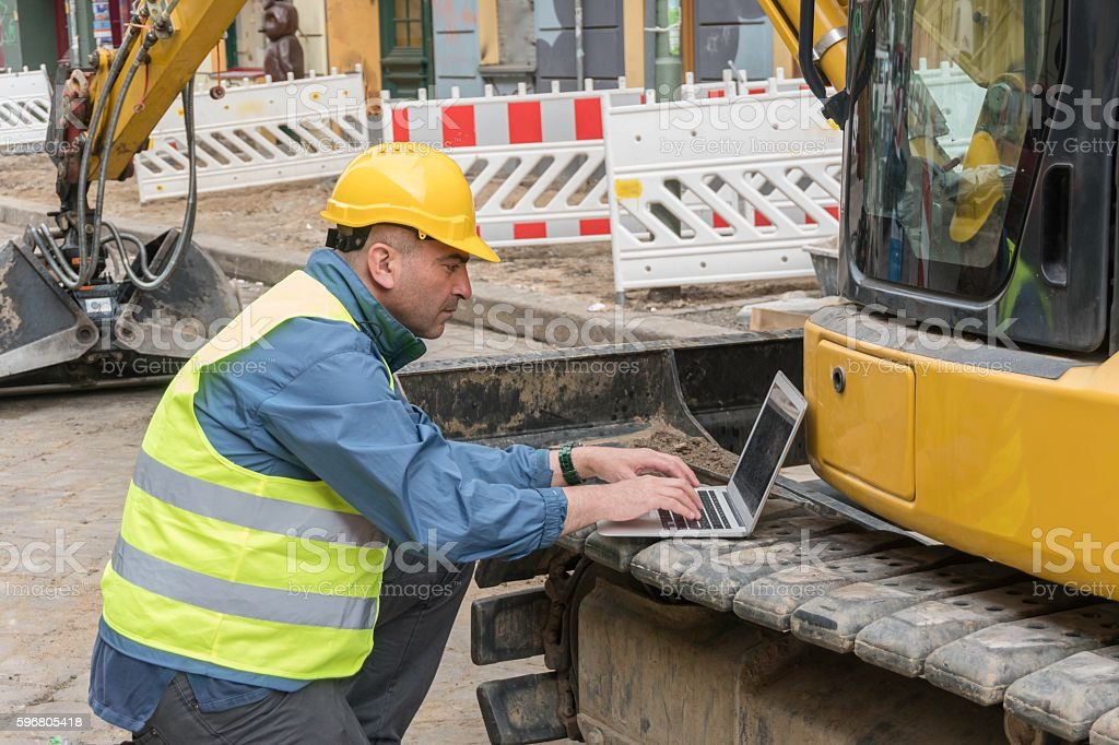 Side view of engineer wearing safety equipment typing on computer stock photo