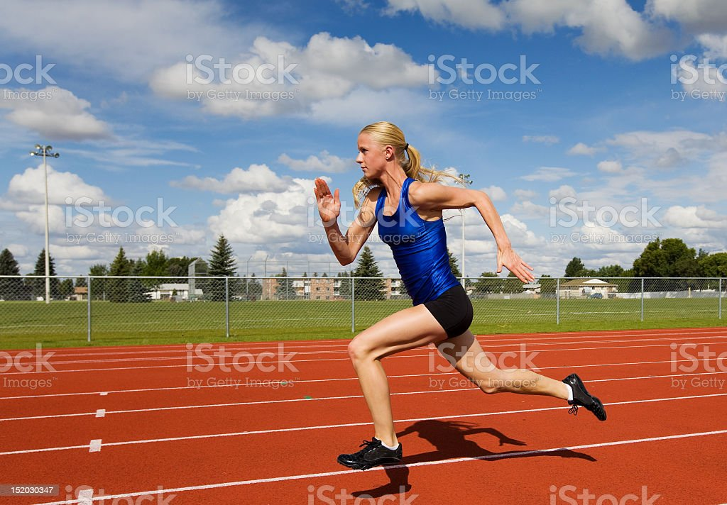 Side view of female athlete sprinting on track stock photo
