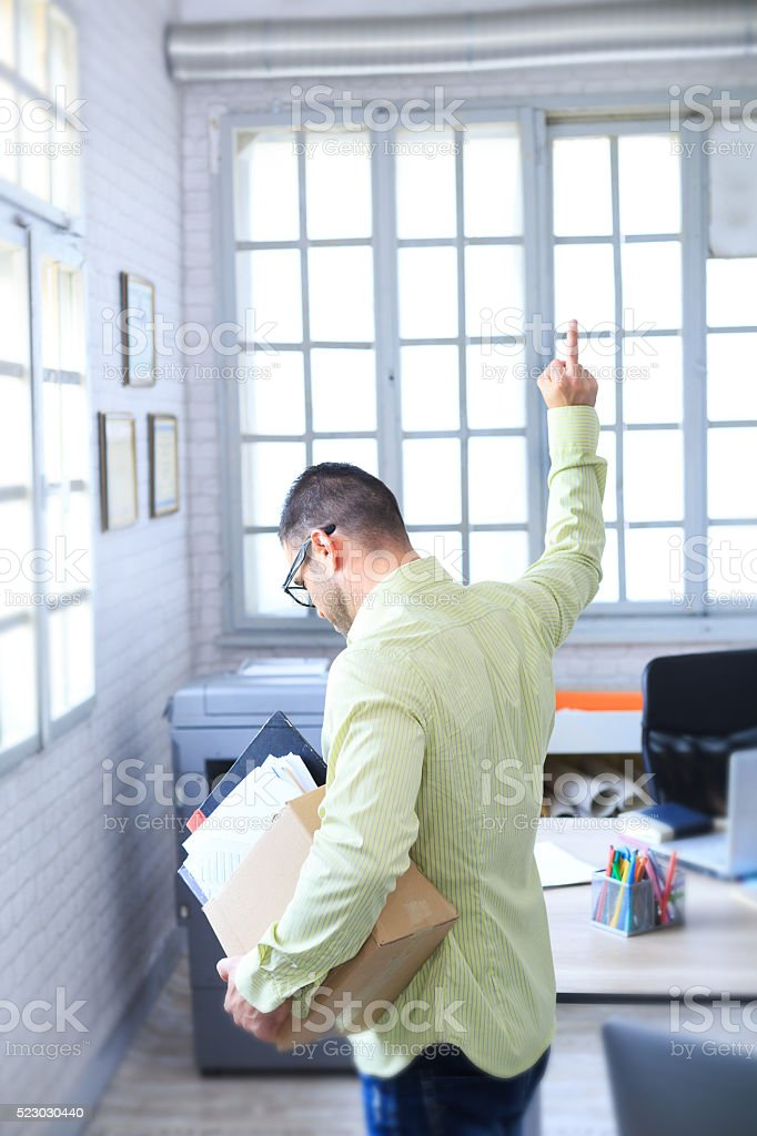 Side view of fired man making obscene gesture stock photo