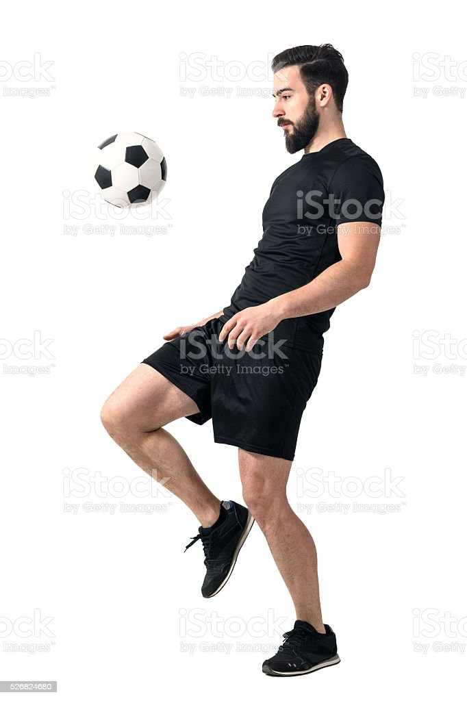 Side view of football player juggling ball with his knee. stock photo