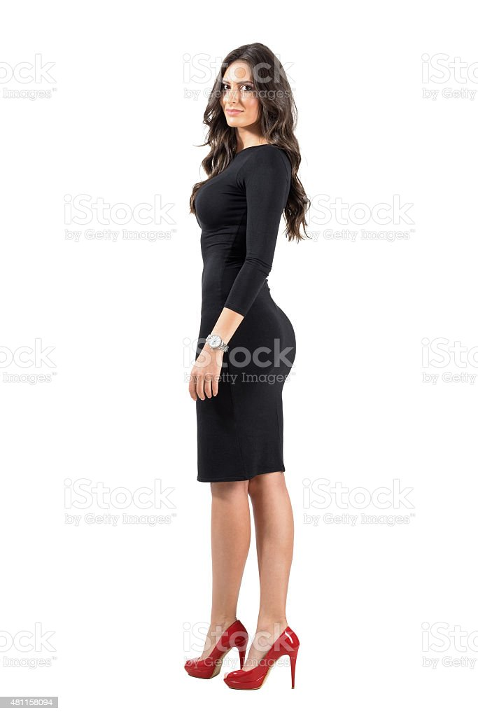 Side view of gorgeous woman walking turning head to camera stock photo