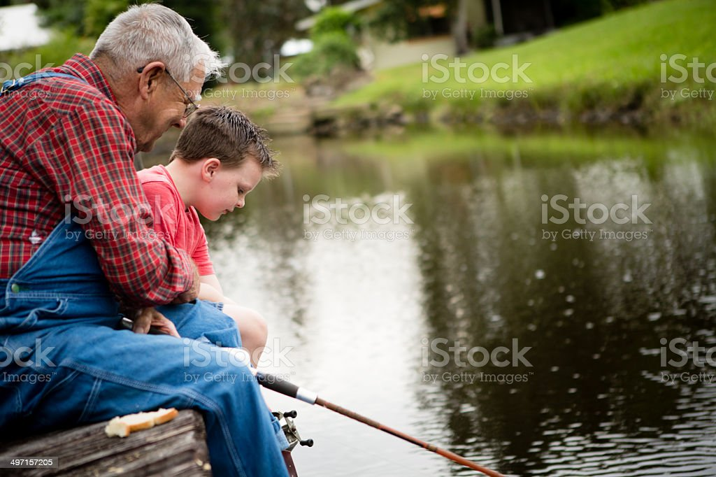 Side View of Grandpa Helping His Great Grandson Fish stock photo
