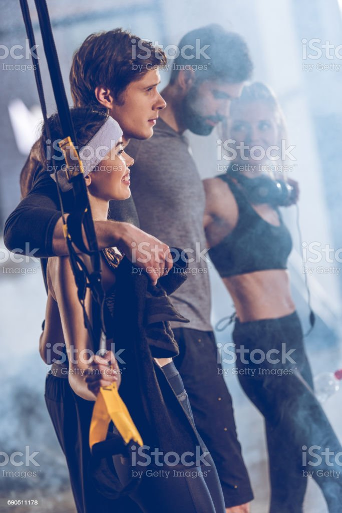 side view of group of sportive people near trx equipment in gym stock photo
