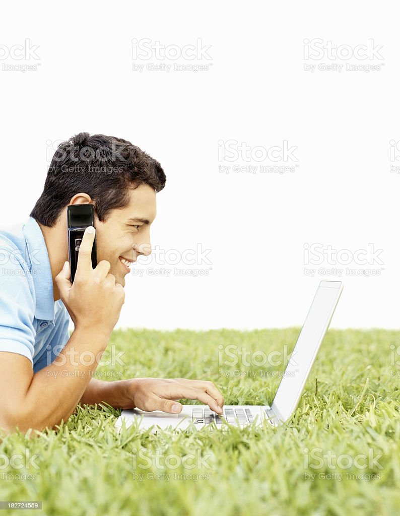 Side view of guy using cellphone and laptop on grass royalty-free stock photo