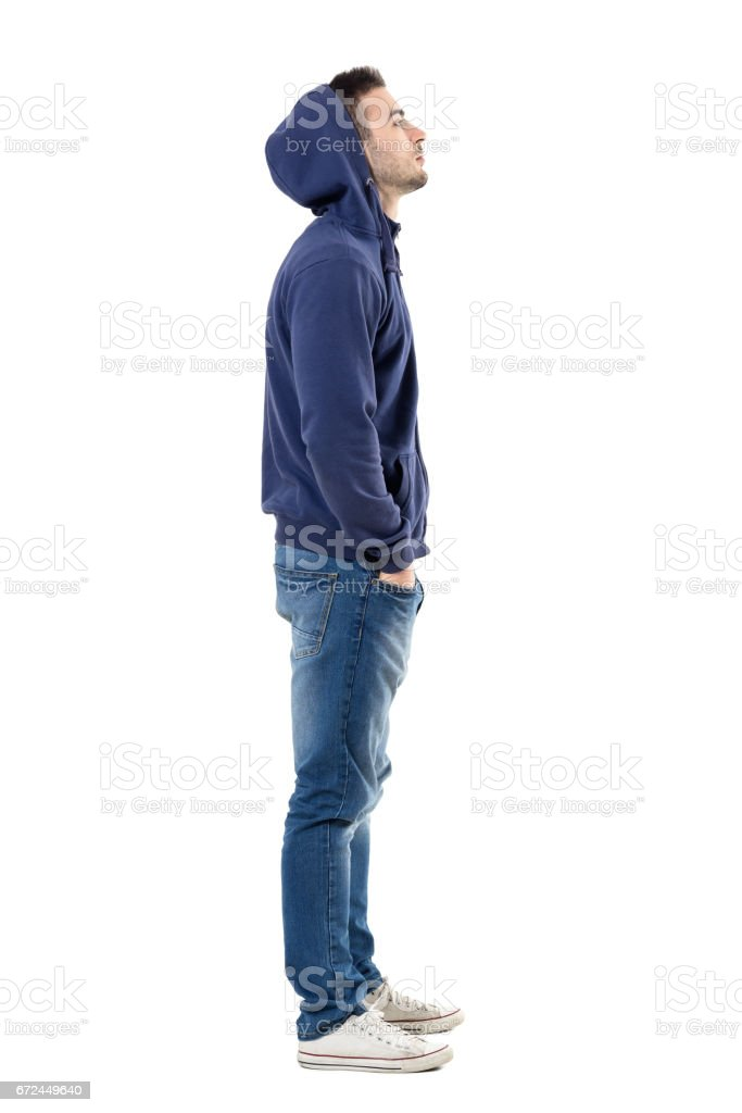 Side view of handsome confident cool young guy with hoodie on head looking up stock photo