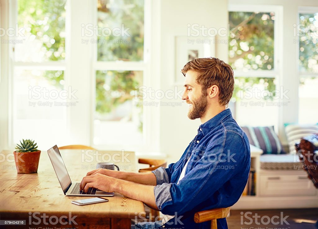 Side view of man smiling while using laptop. Happy male is sitting at...