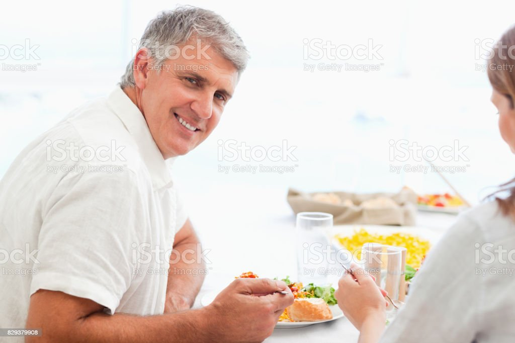 Side view of happy smiling man during dinner stock photo