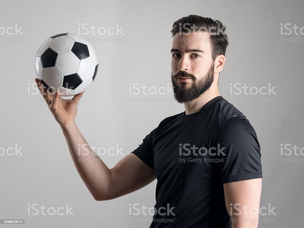 Side view of intense portrait of soccer player holding ball stock photo