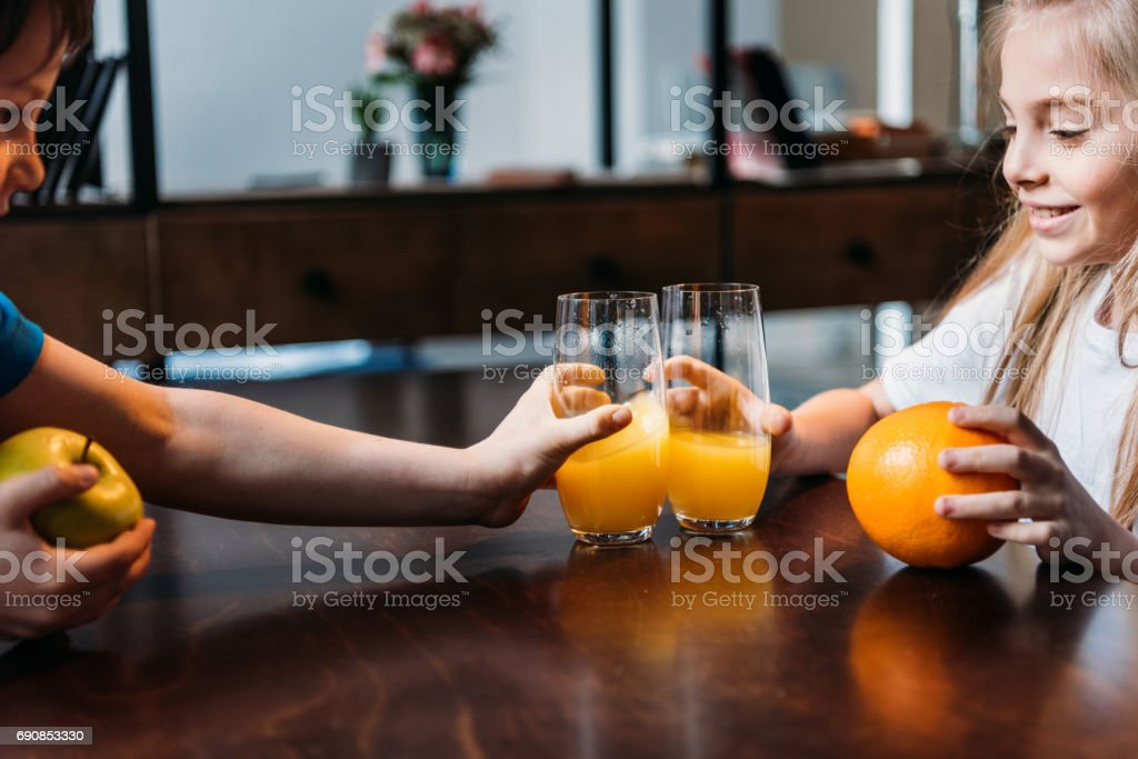 side view of kids clinking glasses with orange juice stock photo