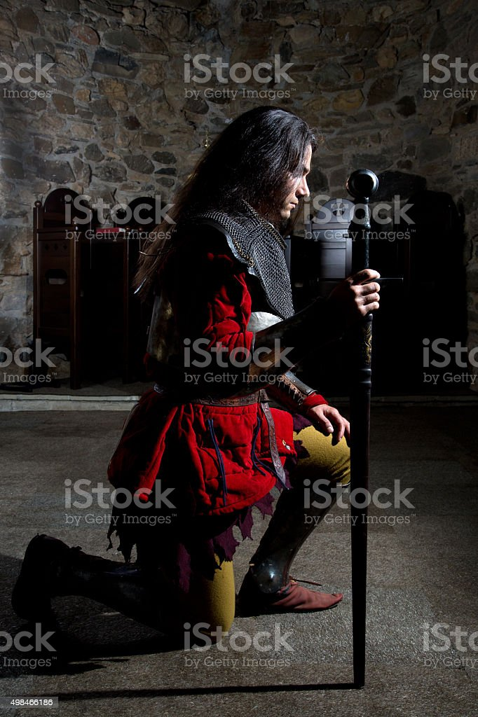Side View of Knight With Sword Praying in Old Church stock photo