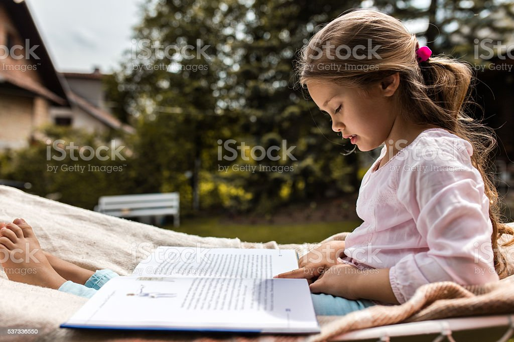 Side view of little girl reading a book in backyard. stock photo