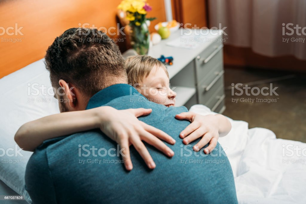 side view of little son hugging father in hospital chamber stock photo